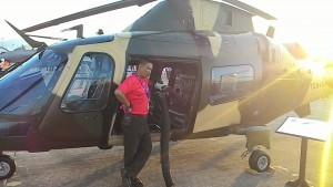A visitor posing with an Army AW109 LOH fitted with a mini gun at LIMA 2015