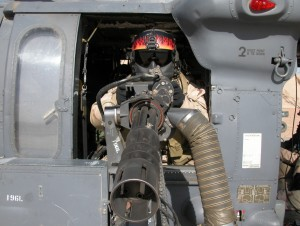 A gunner on a US Army Blackhawk. Note the helmet and the maxillofacial shield.