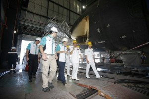 Kamarulzaman (second right) walking inside the hangar where the refit is being conducted. Note the open front end of the submarine.