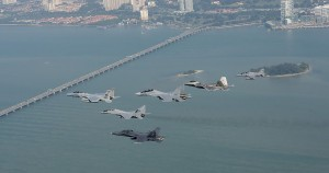 A formation of U.S. Air Force and Royal Malaysian Air Force aircraft including an F-15 Eagle from the 131st Fighter Squadron, 104th Fighter Wing, Barnes Air National Guard Base, Mass., an RMAF SU-30MKM Flanker, a USAF F-22 Raptor from the 154th Wing, Joint Base Pearl Harbor-Hickam, Hawaii, an RMAF MIG-29N Fulcrum, an BAE Hawk, and an RMAF F/A-18 Hornet fly over the Penang Bridge in Penang, Malaysia, during Cope Taufan 14, June 18, 2014.