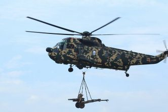 A PUTD Nuri helicopter carrying an Oto Melara 105mm pack howitzer for the firing exercise.