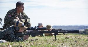 A South Korean soldiers test out the AX sniper rifle under the watchful eye of the Malaysian sniper.