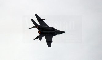 One of the three Fulcrums performing a barrel roll shortly after take off for the flypast.