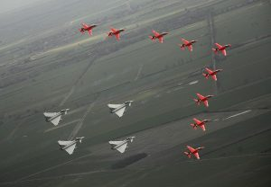 "The Royal Air Force Aerobatic Team (RAFAT) ""The Red Arrows"" and Typhoon aircraft are shown flying in formation as part of the 90th Anniversary of the RAF in 2008."